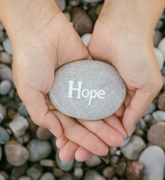 woman-holding-stone-with-the-word-hope-in-her-PHWZNET-min